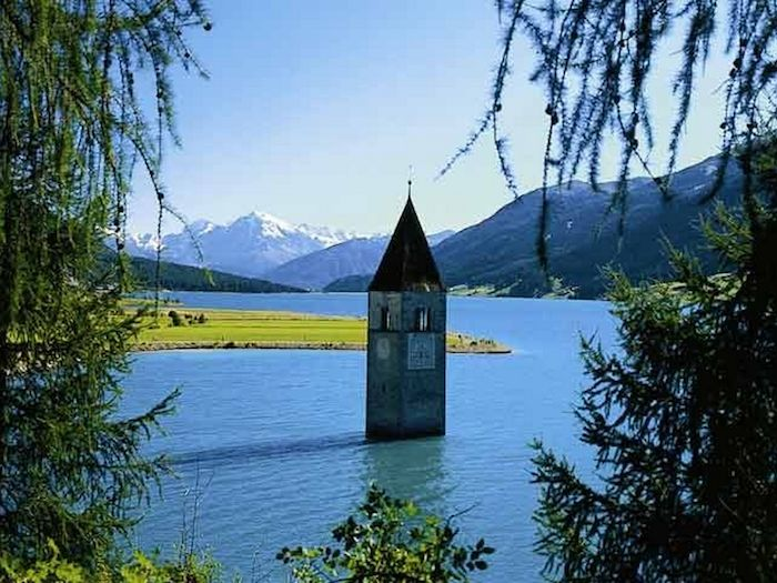 Weird Italy 001CampanileCuron Surreal Places: the old bell tower of submerged Curon Featured Italian History Magazine What to see in Italy  Val Venosta trentino alto adige submerged ghost town semi submerged bell Rio Carlino Mittersee lake resia Josef Duile Curon Graun Curon Venosta curon bell tower of curon bell tower